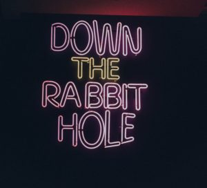 neon sign that says down the rabbit hole.